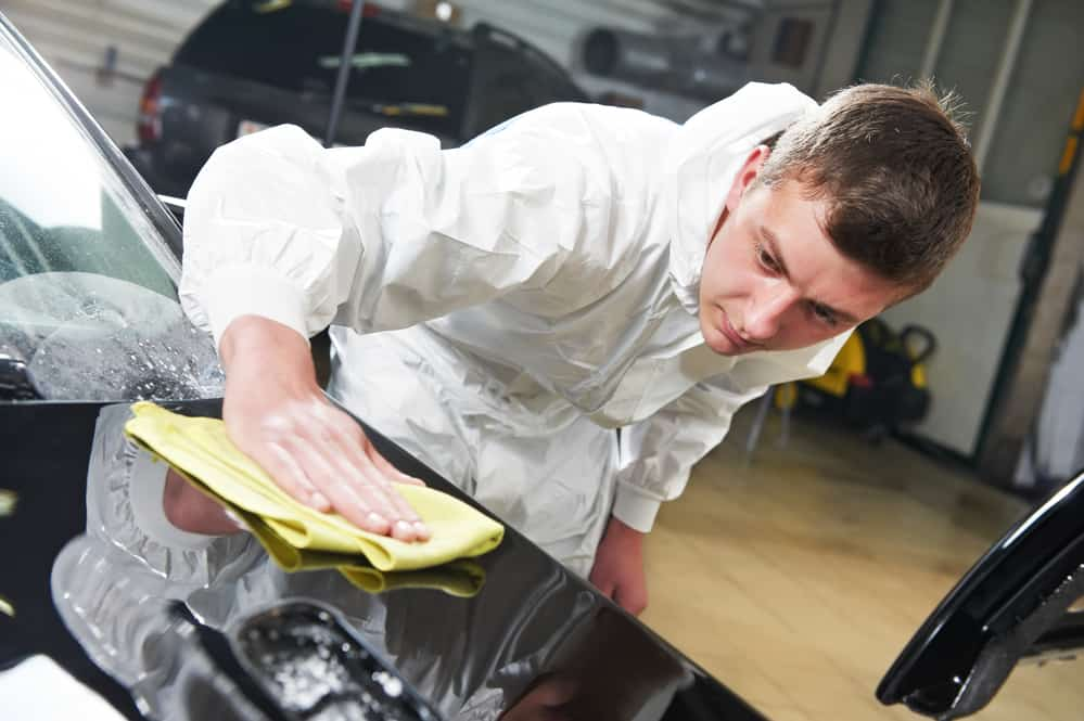 Auto mechanic worker polishing car bonnet with wiper at automobile repair and renew service station shop