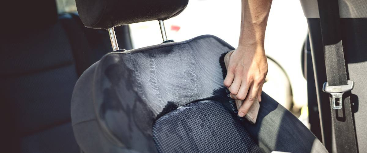 Car care concept - detailing of driver seat using professional tools and cleaners